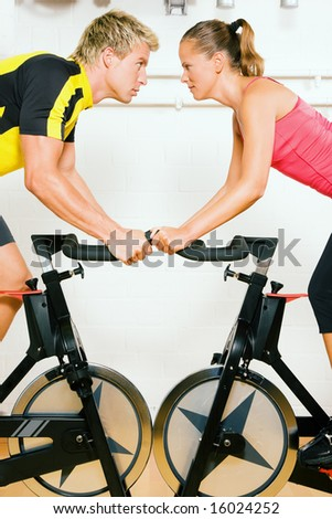 Very competitive couple bicycling in the gym against each other