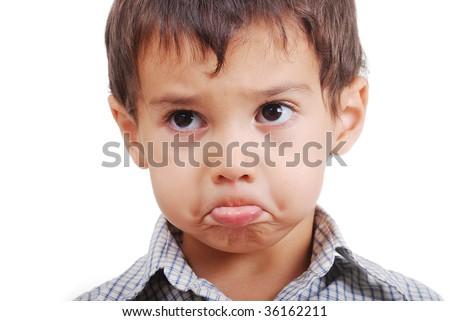 Very cute little boy with angry confused expression on face