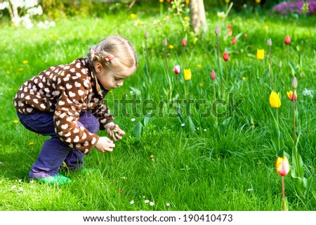 Very cute little girl collecting easter eggs in a flowering garden - stock photo