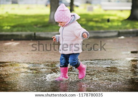 Very cute little girl in pink Jacket, blue jeans and rubber boots is running over a puddle on a rainy day