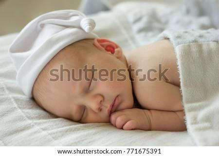 Very cute Two weeks old smiling newborn baby boy portrait sleeping in his  bed. #