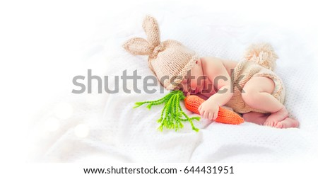 Stock Photo Very cute Two weeks old smiling newborn baby boy wearing knitted bunny costume, hat with rabbit ears, tail and funny carrot toy. Sweet new born baby portrait sleeping in his bed, isolated on white