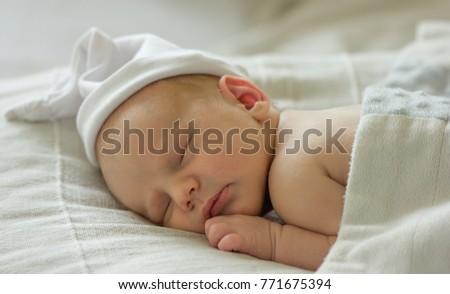 Very cute Two weeks old smiling newborn baby boy wearing knitted costume,  sleeping in his