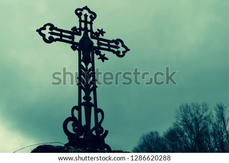 Very dark atmosphere for this cross silhouette. Can illustrate the problems currently encountered by the Christian authority or any article related to ghosts, death, fears, faith. #1286620288