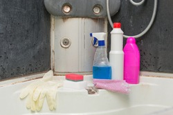 very dirty shower with mold at the joints. There are detergents, sponges and gloves to remove dirt and limescale. The concept is cleaning services, general cleaning, cleaning from old dirt