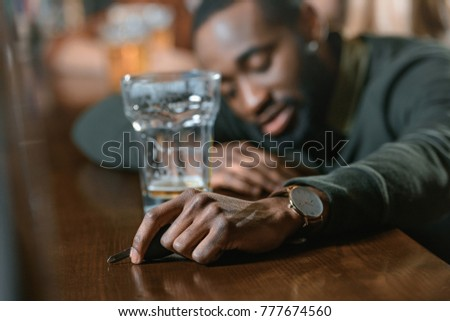 very drunk african american man with automobile keys at bar #777674560