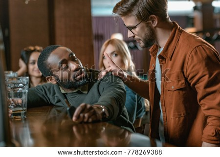 very drunk african american man with automobile keys at bar with friends #778269388