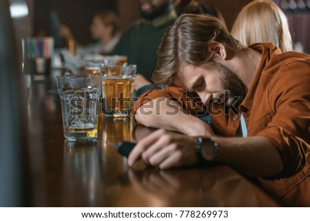 very drunk caucasian man with automobile keys at bar with friends #778269973
