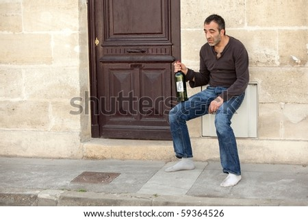 very drunk man standing near house door in the city
