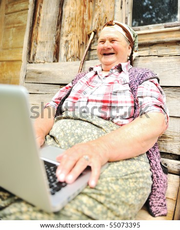 Very elderly woman happily holding a laptop