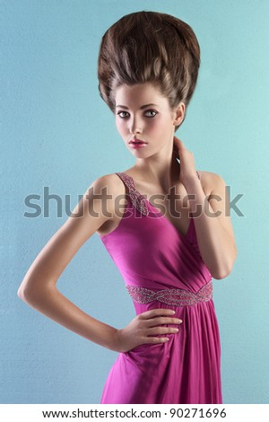 very elegant young woman wearing a pink evening dress and fashion up-do on turquoise background