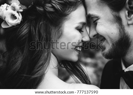 Very emotional black and white photo of a couple in love on the day of their wedding. They smile and touch each other with their foreheads #777137590