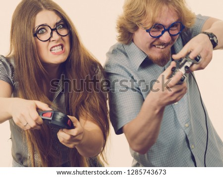 Very emotional couple enjoying leisure time by playing video games together. Studio shot #1285743673