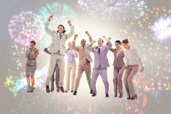 Very enthusiast business people jumping and raising their arms against colourful fireworks exploding on black background