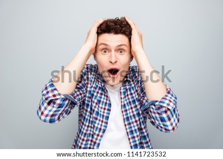 Very excited, surprised man holding hands on head with open mouth looking at camera isolated on light gray background #1141723532