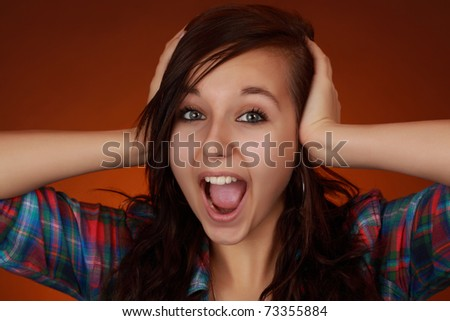 very expressive cute teen girl with hands on her head