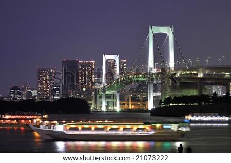 very famous Tokyo landmark, Tokyo Rainbow bridge over bay waters with scenic night illumination and traditional japanese boats