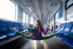 Very flexible wearing mask woman reading book in the subway car sitting in the gymnastic split. Concept of healthy lifestyle, flexibility and yoga