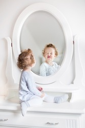 Very funny baby girl with curly hair looking at her reflection in a beautiful white bedroom with a classic dresser with a round mirror