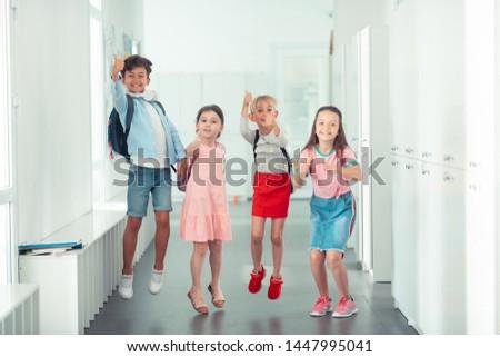 Very good mood. Cheerful good-looking children having very good mood before summer holidays