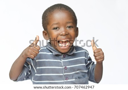 Very happy African black boy making thumbs up sign with hands laughing happily (African ethnicity black boy isolated on white)