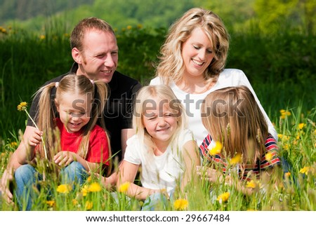 Very happy family with three kids sitting in a meadow with dandelion