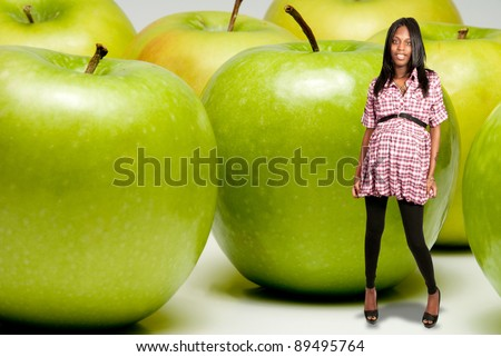Very happy pregnant black African American woman with some Granny Smith green apples