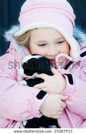 Very happy young girl hugging an border collie puppy