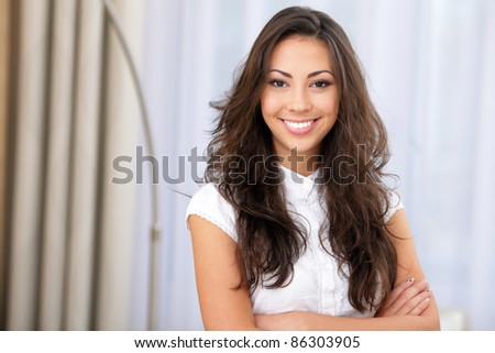 Very happy young woman standing with arms crossed