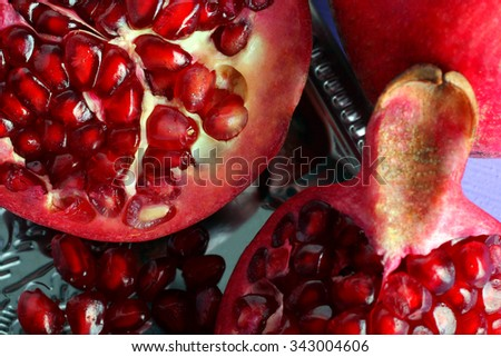very juicy and big and delicious pomegranate in the section in the tray isolated on purple background #343004606