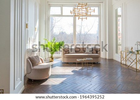 very light and bright interior of luxurious cozy living room with chic soft beige furniture with gold metallic elements, huge window to the floor and wooden parquet Photo stock ©