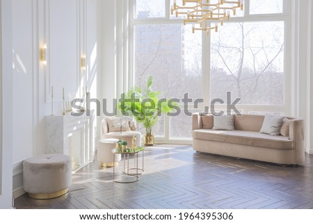 very light and bright interior of luxurious cozy living room with chic soft beige furniture with gold metallic elements, huge window to the floor and wooden parquet Stock photo ©