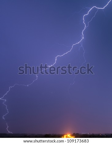 Very long and tortuous lightning striking a ground object in distance