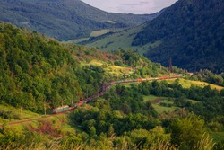 Very long cargo train on curves and turned on the mountain pass. Train like a snake in mountain railway with many carriages in Carpathian Mountains peak. Logistic and transportation, silk way