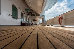 Very low ground view of a long cruise ship deck, with white life boat above and life saver ring on right side, with a dramatic blue, cloudy sky.
