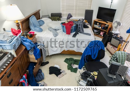 Photo of  Very messy, cluttered teenage boy's bedroom with piles of clothes, music and sports equipment.