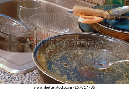 Very messy kitchen with piles of dirty dishes