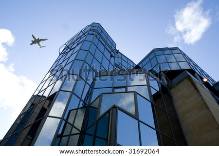 Very modern building in a financial district with blue skys and airplane flying past