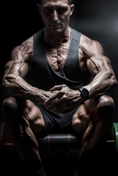 Very muscular bodybuilder man with veins on the body sitting in dim light. Gym training. Fit and lean body.