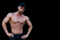 Very muscular fitness model man, posing without shirt. there is a black background