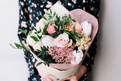 Very nice florist woman holding a beautiful colourful blossoming flower bouquet of fresh Quicksand roses, carnations, ranunculus, peony, pistachio leaves on the grey wall background