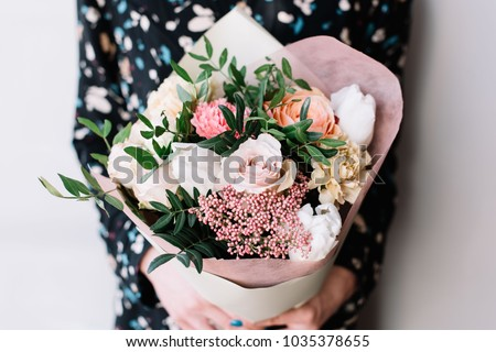 Very nice florist woman holding a beautiful colourful blossoming flower bouquet of fresh Quicksand roses, carnations, ranunculus, peony, pistachio leaves on the grey wall background #1035378655