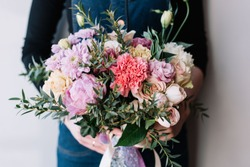 Very nice florist woman holding a beautiful colourful blossoming flower bouquet of peony, carnations, roses, eustoma, chrysanthemums, pistachio leaves on the grey wall background