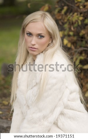 very nice girl wearing a white fur in a winter day in park