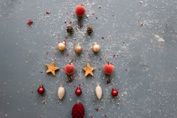Very nice minimalistic Christmas tree formed out of red and silver ornamentals in the shape on pine cones, stars, apples on the grey background. Dusted with snow, top view, flat lay