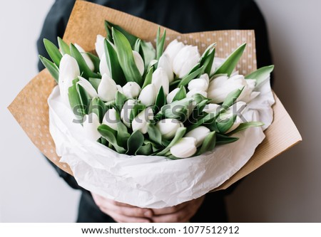 Very nice young man in a black shirt holding a huge blossoming flower bouquet of fresh white tulips on the grey wall background #1077512912