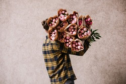 Very nice young man in a plaid yellow shirt holding huge pile of many pink peony bunches wrapped in craft paper, cropped photo, bouquet close up
