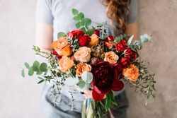 Very nice young woman holding a beautiful flower bouquet of fresh roses, peony, eucalyptus  in pastel cream, orange and vivid red colors on the grey background