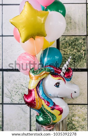 Very nice young woman holding a huge colourful inflatable festive smiling unicorn balloon