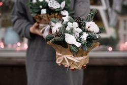 Very nice young woman holding beautiful festive arrangement of fresh spruce in a box with cotton, stars, decorative bird, pine cone, fake snow and glitter